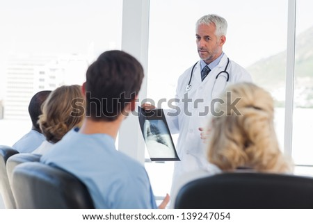 Doctor presenting x-ray during a meeting - stock photo