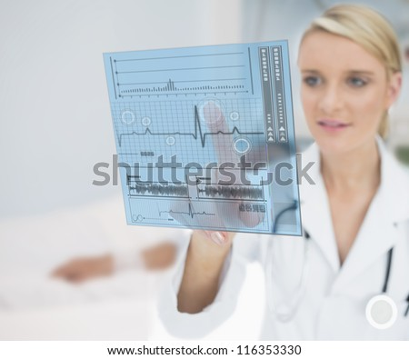 Doctor pressing on ECG line interface hologram - stock photo
