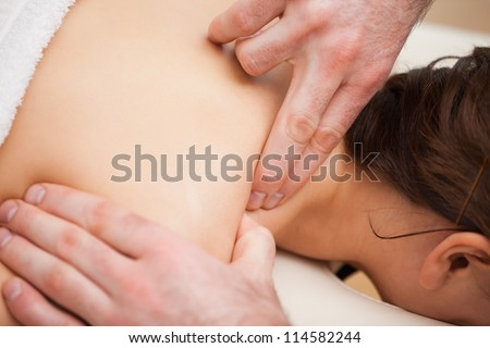 Doctor pressing the shoulder of his patient in a room - stock photo