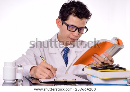 Doctor reading a medical book,Doctor Filling The Medical Form (shallow DOF)  - stock photo