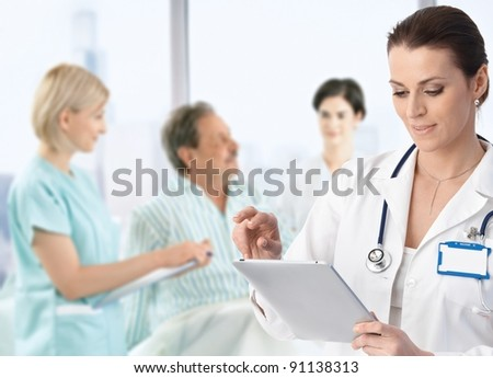 Doctor recording information to electronic tablet at patients bed, team working in background.? - stock photo