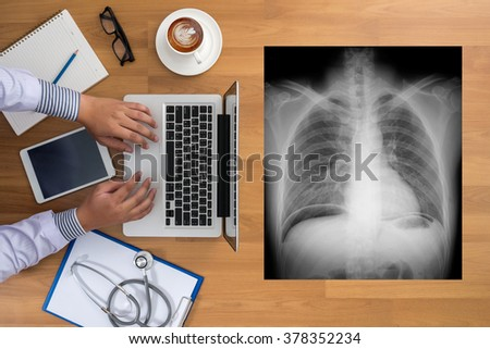 Doctor's desktop with medical equipment, computer and X-ray top view - stock photo