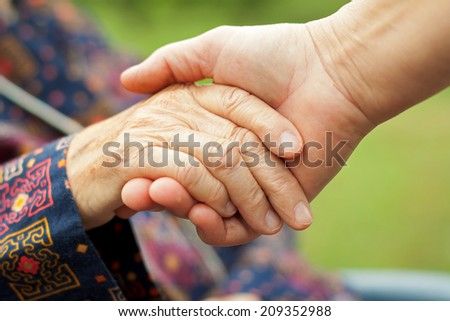 Doctor's hand holding a wrinkled elderly hand - stock photo