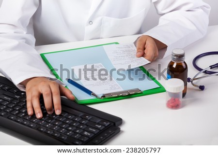 Doctor's hand typing on keyboard in surgery