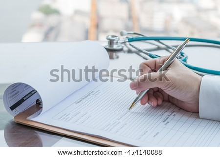 Doctor's hand working using pen writing on patient's discharge blank paper form, medical prescription, stethoscope on table/ desk: Physician taking note on empty paperwork in hospital/ clinic interior - stock photo