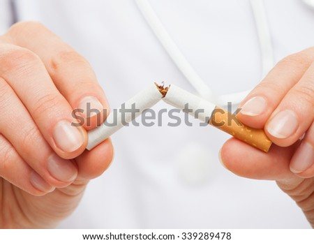 Doctor's hands holding a broken cigarette, healthy lifestyle concept - stock photo