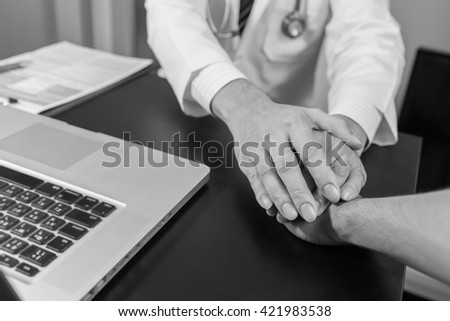 doctor's hands holding  patient's hand for encouragement and empathy. - stock photo