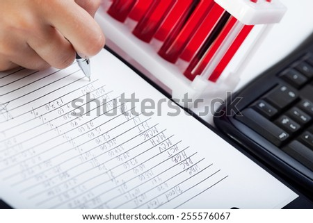 Doctor's medical notes with background of blood samples
