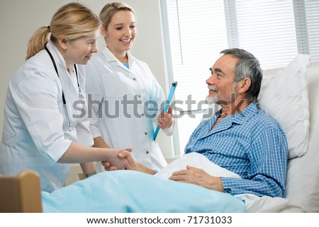 doctor shakes hands with patient in hospital bed - stock photo