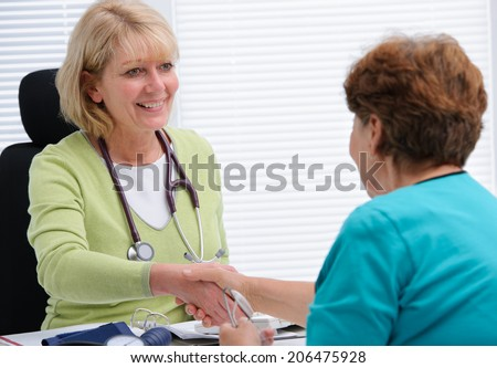 Doctor shaking hands to patient in the office - stock photo