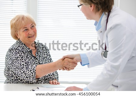 Doctor shaking hands with patient in the office - stock photo