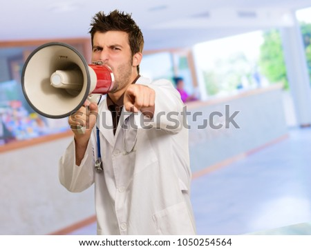 Doctor Shouting In Megaphone And Gesturing, Indoors