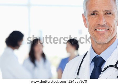 Doctor showing a beaming smile with his medical interns behind him - stock photo