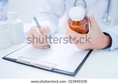 doctor showing a bottle of pills to the patient - stock photo