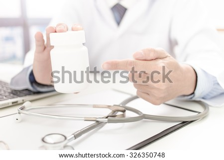 doctor showing a bottle of pills to the patient