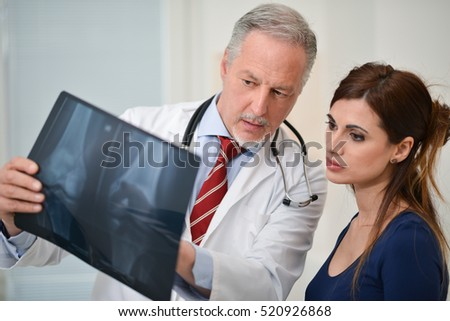 Doctor showing a radiography to his patient in his studio