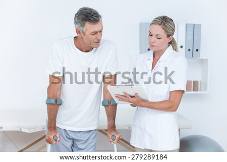 Doctor showing clipboard to her patient with crutch in medical office - stock photo