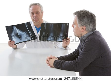 Doctor showing diagnosis of x-ray image to patient sitting at office desk.