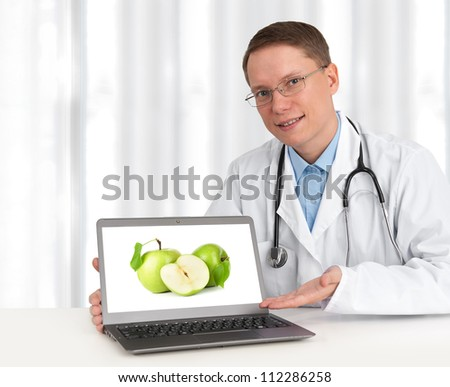 doctor showing green apples on his laptop computer - stock photo