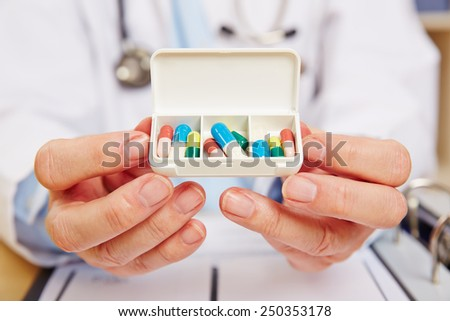 Doctor showing pill dispenser filled with medication in his hands - stock photo