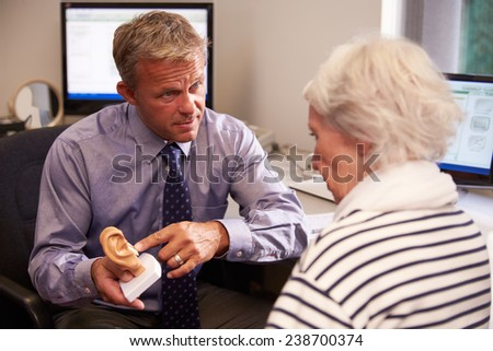 Doctor Showing Senior Female Patient Model Of Human Ear - stock photo