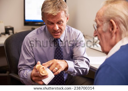 Doctor Showing Senior Male Patient Model Of Human Ear - stock photo