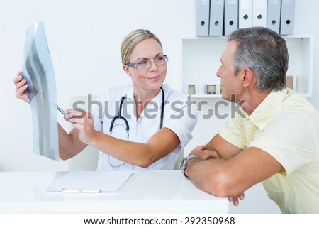 Doctor showing X rays to her patient in medical office