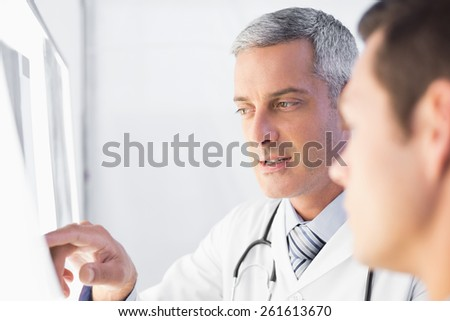 Doctor showing X rays to his patient in medical office - stock photo