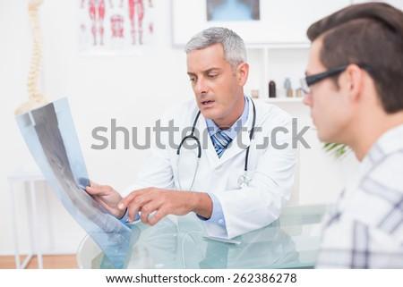 Doctor showing Xrays to his patient in medical office - stock photo