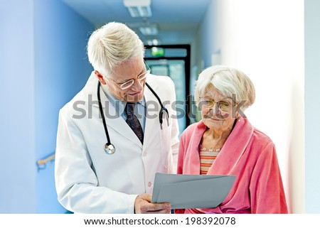 Doctor Shows Female Elderly Patient Results while standing in hospital corridor. - stock photo