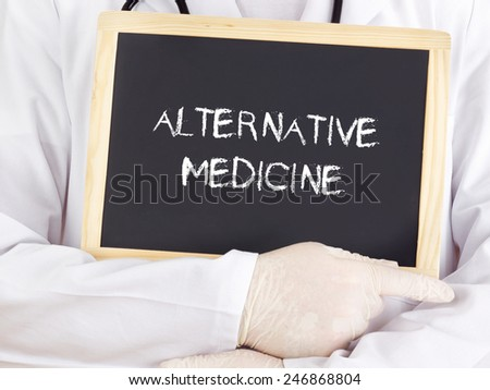 Doctor shows information on blackboard: alternative medicine - stock photo