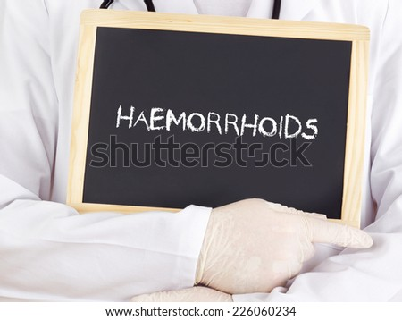 Doctor shows information on blackboard: haemorrhoids - stock photo