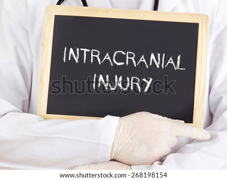 Doctor shows information on blackboard: intracranial injury - stock photo