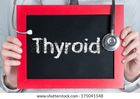 Doctor shows information on blackboard: thyroid  - stock photo