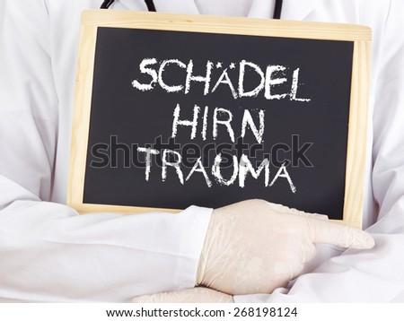 Doctor shows information: traumatic brain injury in german - stock photo