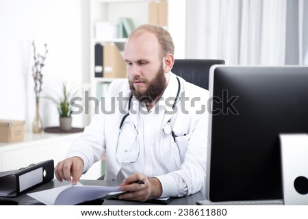Doctor sitting at desk checking time planner