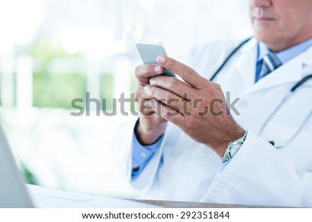 Doctor sitting at his desk and texting in medical office