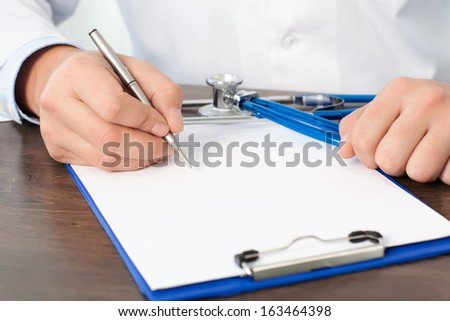 Doctor sitting at his desk with a stethoscope and writing something on a white sheet - stock photo