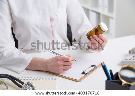 Doctor sitting at table and making notes, container with pills in hand, stethoscope on table. No head seen. Concept of writing prescription.