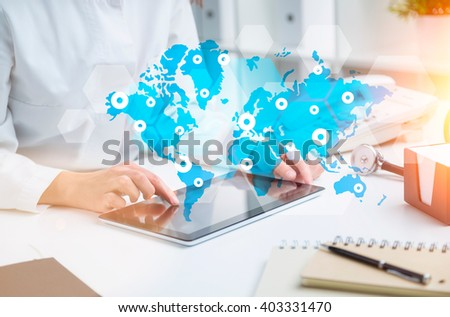 Doctor sitting at table and working with tablet. World map with points in front. Only hands seen. Concept of medical help. - stock photo