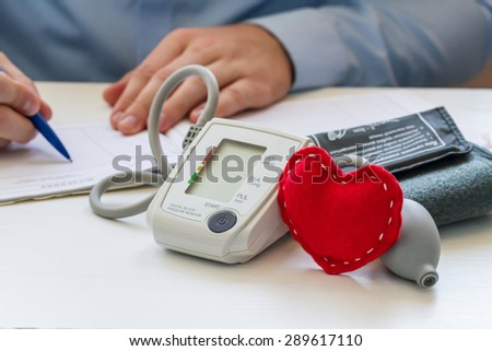 Doctor sitting at the white table with digital blood pressure monitor and red soft heart and writing a prescription - stock photo