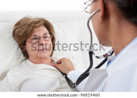 Doctor sitting in bed, examines recovering senior patient - stock photo