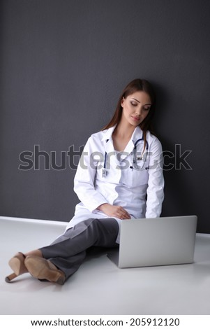 Doctor sitting on the floor near wall with laptop