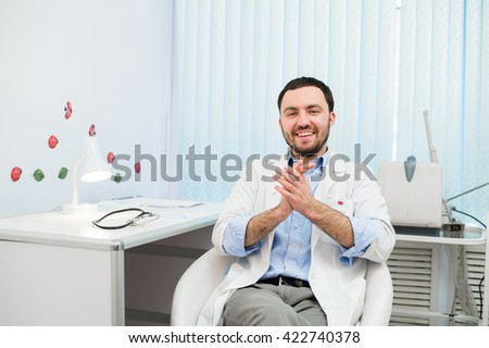 Doctor sitting relaxed in his chair in the office and smiling - stock photo
