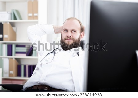 Doctor sitting relexed at desk, hands behind head