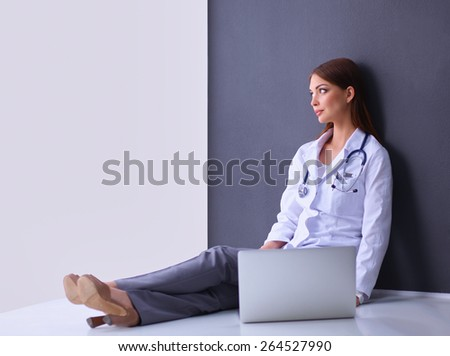 Doctor sitting  the floor near wall  with laptop  - stock photo