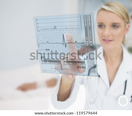 Doctor smiling and touching ECG interface hologram - stock photo