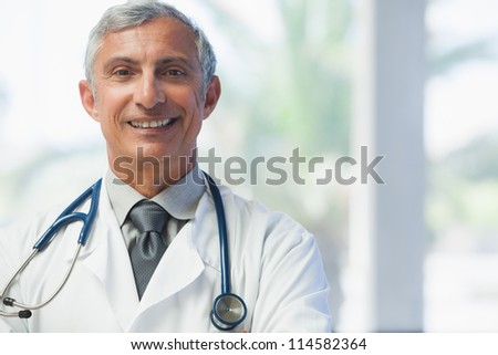 Doctor smiling in hospital - stock photo