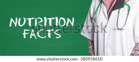 Doctor Standing front of Chalk Board written NUTRITION FACTS - stock photo