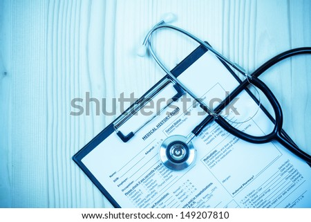 Doctor stethoscope, clipboard with medical records form on wood - stock photo